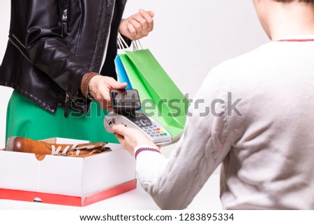Woman buys shoes at the shop checkout, she is paying using a phone.