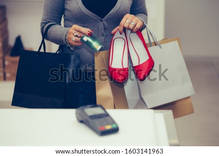 Woman buys shoes with high heels at the shop checkout, she is paying using a credit card.