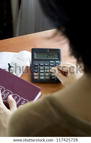 woman calculating receipts on desk