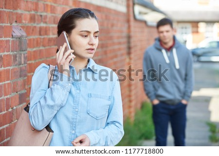 Woman Calling For Help On Mobile Phone Whilst Being Stalked On City Street By Man