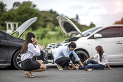 Woman calls for help and for insurance agent to quick attention in the spot of accident after both cars crashed occurrence with injured people in background