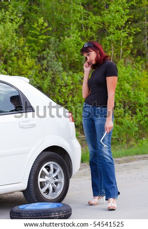 Woman calls to a service standing by a white car.