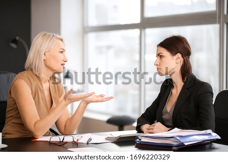 Woman calming her fired mature colleague in office