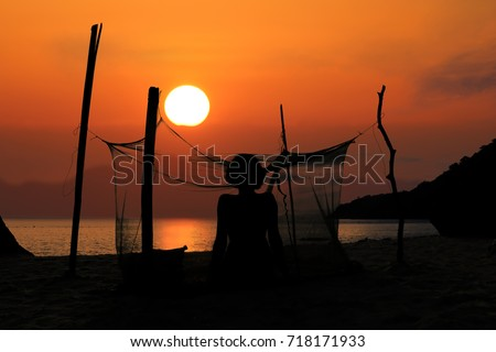 Woman camping alone on the beach with mosquito net, Red sky sunset background.