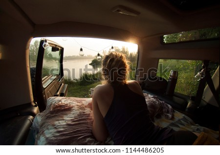 Woman camping in the camper car and drinking morning coffee. Beautiful calm lake in the background. Sunrise mild natural light.  Wild camping concept. Horizontal image.