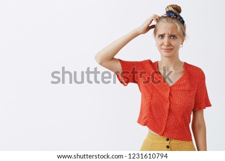Woman cannot get joke, standing clueless and confused scratching head and gazing worried and concerned at camera, frowning and pursing lips, posing over gray background in vintage polka-dot clothes