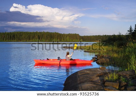 Woman canoeing in a beautiful lake at sunset