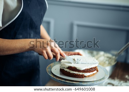 woman carefully icing the cake...