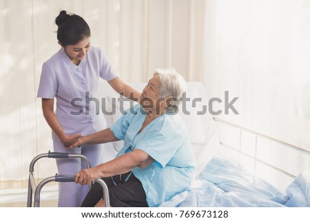 woman caregiver and elderly patient on examination couch. Happy nurse holding hand of senior to help senior patient. female nurse supporting senior disabled woman with walker at hospital. Health care