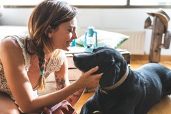 Woman Caressing her Dog at Home. Middle Age Woman Kissing her Dog on the Floor. Black Guide Dog at Home. Lifestyle Concept.