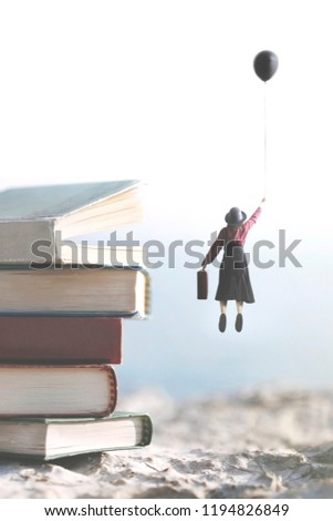 woman carried by a balloon flies above a mountain of giant books #1194826849