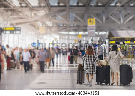 woman carries luggage at the airport terminal.