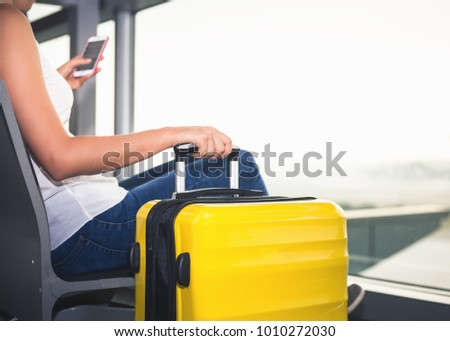 Woman carries your luggage at the airport terminal of Hong Kong, after gonna stady or education fly to Singapore. Use a mobile phone looking for flight #1010272030