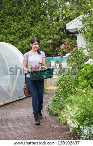 Woman carrying a basket of plants while walking on garden center plant