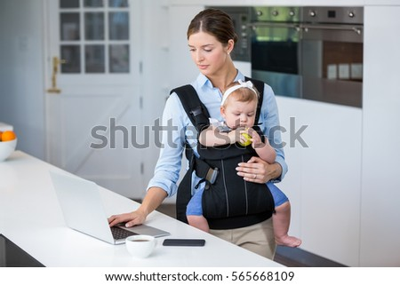Woman carrying baby girl while using laptop at table in house