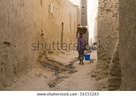 Woman carrying basket on head in narrow street