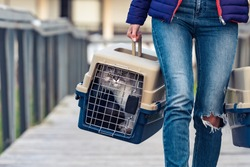 Woman carrying her cat's in a special plastic cage or pet travel carrier. Moving a cat to a new house