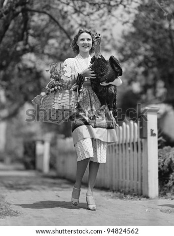 Woman carrying live turkey and grocery basket