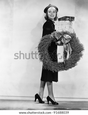 Woman carrying packages and Christmas wreath