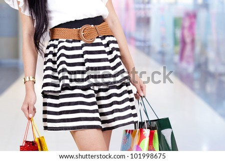 Woman carrying shopping bags isolated over white