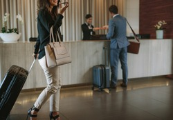 Woman carrying suitcase and talking on mobile phone in a hotel lobby. Traveler female walking with her luggage in hotel hallway.
