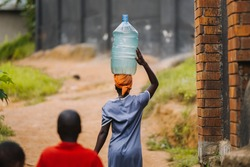 woman carrying water can in Uganda, Africa