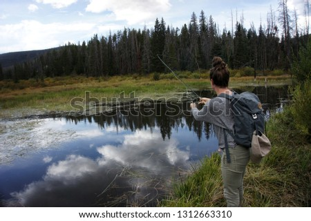 Woman casting a fly rod. Fly fishing girl casting a fly rod. Fly fishing small pond. Fishing lakes.