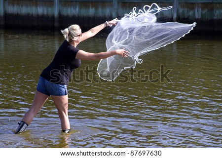 Woman casting net for bait to be used for surf fishing