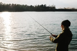 Woman catching a fish, pulling rod while fishing. Girl fishing from beach lake or pond with text space.Fisherman with rod, spinning reel on the river bank. Sunset. Fishing for pike, perch, carp.
