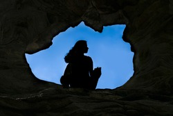 Woman Caver Spelunker exploring inside of a Dark Cave. female sitting at the edge of the cave hole. Oval shaped of cave hole.Silhouette of a girl standing in front of the entrance to the cave. Freedom