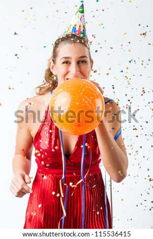 Woman celebrating birthday at a shower of confetti with balloon and smiling