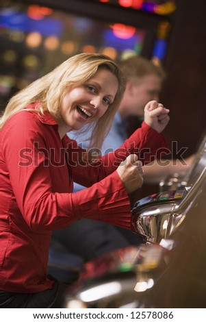 Woman celebrating win at slot machine in casino