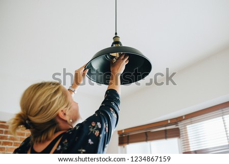 Woman changing a light bulb in her home