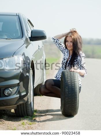 Woman changing car wheel at road