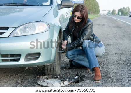 woman changing the broken Tire