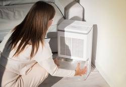 Woman changing water container in air dryer, dehumidifier, humidity indicator. Humid air at home.