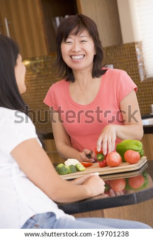 Woman Chatting To Friend While Preparing meal,mealtime
