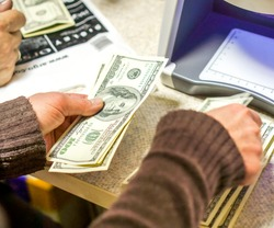 woman check bills on big white bill detector with violet light. woman hands took dollars into bill detector. New Dollar in the Money Detector in the Exchange Office