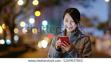 Woman check on smart phone in city at night