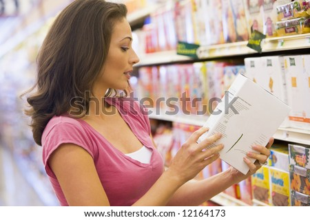 Woman checking food labelling in supermarket - stock photo