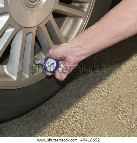 Woman checking her tire pressure to help increase her  gas mileage gauge indicates low pressure