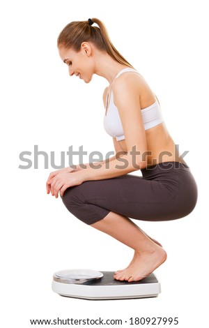 Woman checking her weight. Side view of beautiful young woman in sports clothing checking her weight while crouching on scale