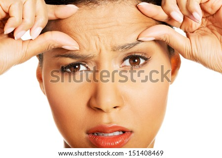 Woman checking her wrinkles on her forehead - isolated on white  - stock photo