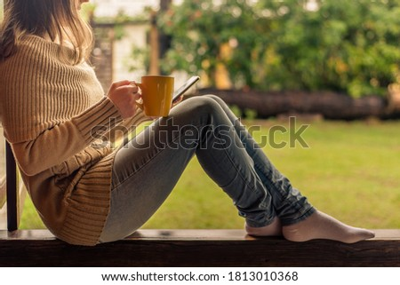 Woman checking mobile phone and drinking coffee by the morning stock photo