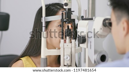 Woman checking on eye in clinic