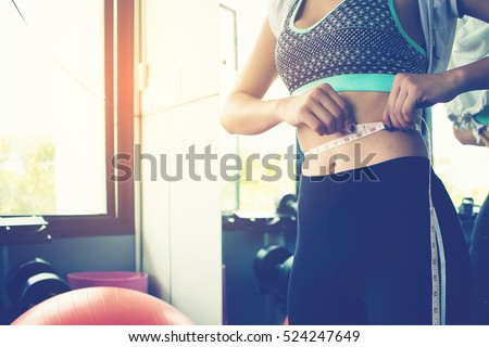 woman checking success of weight loss program with measuring tape at gym.