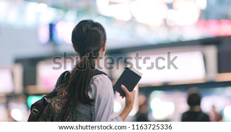 Woman checking the flight number on screen board in the airport