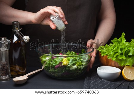 Woman chef in the kitchen preparing vegetable salad. Healthy Eating. Diet Concept. A Healthy Way Of Life. To Cook At Home. For Cooking. The girl sprinkles salt in a salad on a dark background Foto d'archivio ©