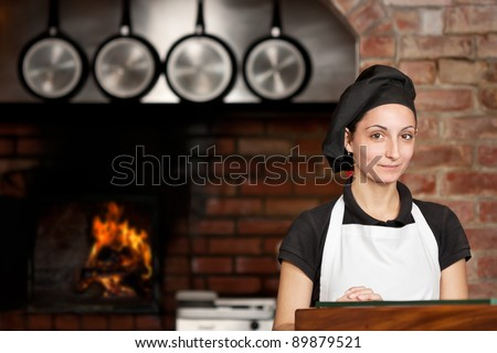 Woman Chef is standing at the kitchen entrance with the wood oven in the background in a pizza restaurant kitchen