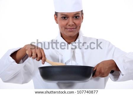 Woman chef stirring a wok